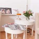 Bild von einem Empfangsraum in einem Kosmetikstudio mit zwei hellen Sesseln, weißem Tisch, mit Blumen drauf und Zeitschrifften